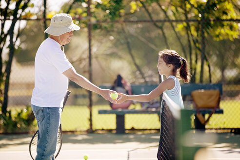 Granddaughter giving tennis ball to grandfather at court - CAVF25812