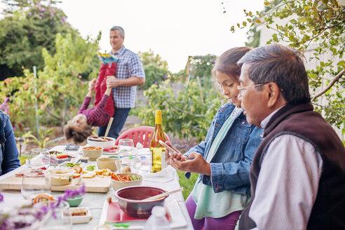 Multi-generation family enjoying at dining table in backyard - CAVF25824