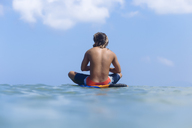 Indonesia, Bali, surfer sitting on surfboard - KNTF01102