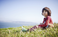 Thoughtful boy looking away while sitting on grassy field - CAVF25965