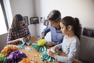 High angle view of girls with father making paper flowers while sitting at table - CAVF26046