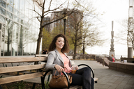 Portrait of happy businesswoman sitting on bench by footpath - CAVF26265