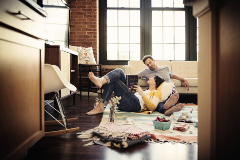 Smiling couple relaxing on carpet at home - CAVF26313