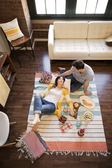 High angle view of couple relaxing by food on carpet - CAVF26316