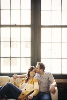 Man kissing girlfriend while sitting on sofa at home - CAVF26319