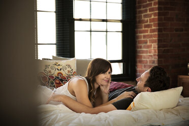 Smiling couple relaxing on bed at home - CAVF26325