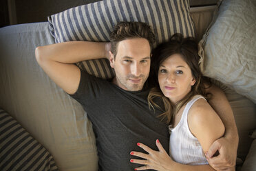 Portrait of couple embracing and relaxing on bed at home - CAVF26328