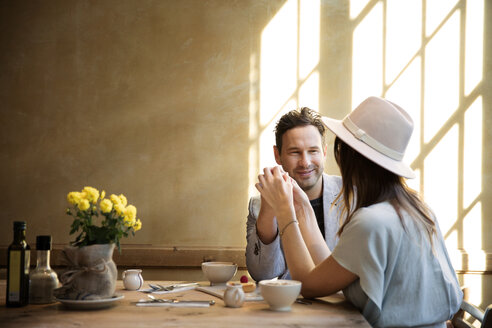 Happy couple holding hands and sitting by table in restaurant - CAVF26331