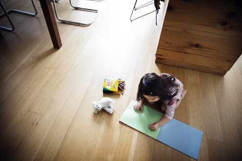 High angle view of girl studying on wooden flooring at home - CAVF26334