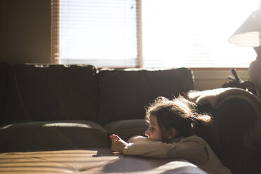 Bored girl sitting on floor by sofa at home - CAVF26400