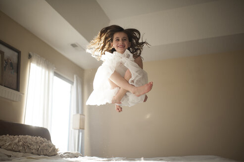 Happy girl jumping on bed at home - CAVF26403