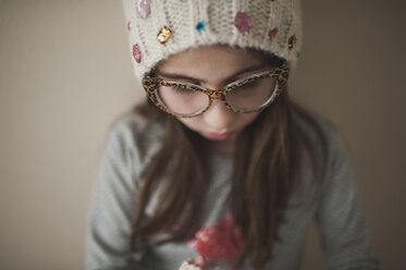Close-up of girl wearing eyeglasses and knit hat while standing against wall at home - CAVF26406