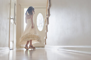 Girl in dress spinning by door at home - CAVF26421