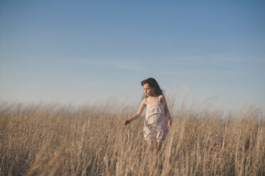Girl touching dry grass while walking on field against blue sky - CAVF26424