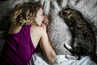 High angle view of woman and cat sleeping on bed at home - CAVF26502
