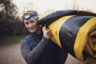 Portrait of happy woman carrying folded inflatable kayak in forest - CAVF26649