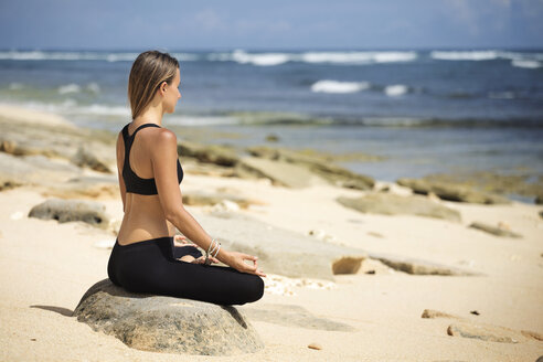 Side view of woman meditating in lotus position on beach during summer - CAVF26708