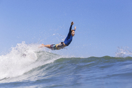 Side view of male surfer jumping on sea against clear blue sky - CAVF26729