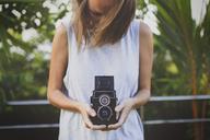 Woman holding vintage camera at yard - CAVF26741