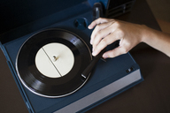 Cropped image of woman playing record player on table - CAVF26744