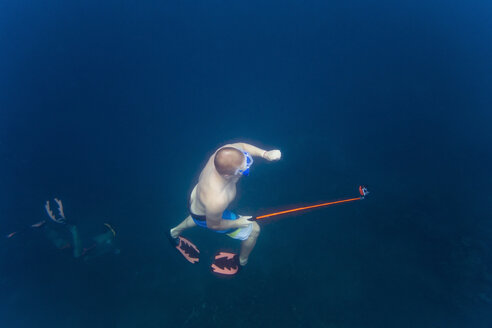 High angle view of man holding monopod while swimming with friends undersea - CAVF26783
