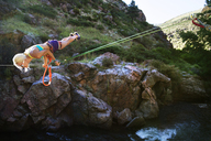 Woman balancing on rope while slacklining over river - CAVF26873