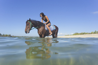 Indonesia, Bali, Woman sitting on horse, in water - KNTF01105