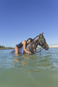 Indonesia, Bali, Woman lying on horse, in water - KNTF01111