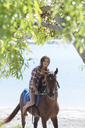 Indonesia, Bali, Woman riding a horse at beach - KNTF01117