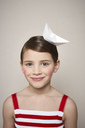 Portrait of smiling little girl with paper boat on her head - FSF01002