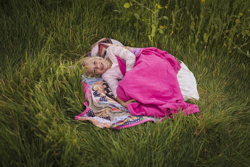 High angle portrait of happy girl lying on blanket amidst grassy field - CAVF26941