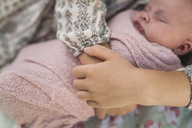 Cropped hands of sister holding newborn baby - CAVF26965