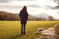Rear view of woman and dog standing on grassy field against sky - CAVF27058
