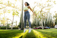 Woman jumping while exercising in park - CAVF27133