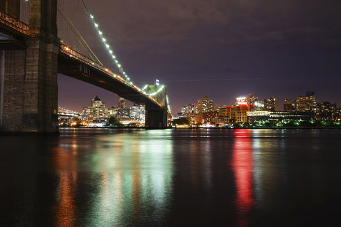 Illuminated Brooklyn Bridge over river against illuminated city - CAVF27216