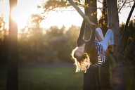 Portrait of girl hanging on branch at park - CAVF27249