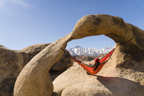 Woman relaxing on hammock hanging from rock formation - CAVF27273