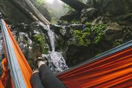 Low section of woman relaxing on hammock by stream in forest - CAVF27288