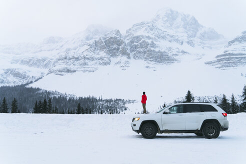 Side view of hiker standing on snow covered field by off-road vehicle during winter - CAVF27327