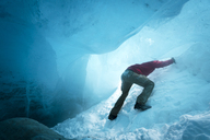 Low angle view of hiker ice climbing in cave - CAVF27333
