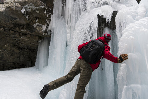 Rear view of man with backpack standing by frozen waterfall over mountain - CAVF27342