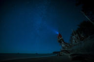 Hiker wearing headlamp sitting on tree trunk at La Push beach against sky at night - CAVF27348