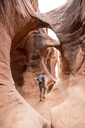 Rear view of woman with backpack hiking in rock formations - CAVF27384