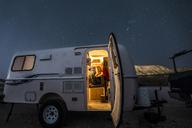 Woman sitting in illuminated camper trailer against star field - CAVF27387
