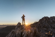 Rear view of female hiker standing on cliff against clear sky during sunrise - CAVF27408
