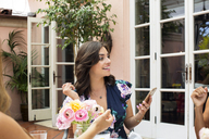 Happy woman holding smart phone at outdoor restaurant talking with friends - CAVF27429