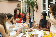 Cheerful female friends enjoying lunch at outdoor restaurant - CAVF27432