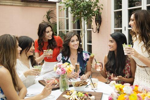 Cheerful female friends enjoying lunch at outdoor restaurant - CAVF27432
