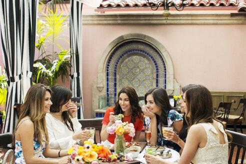 Cheerful females talking at outdoor restaurant - CAVF27435