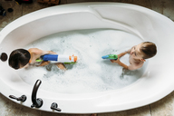 Overhead view of brothers playing with squirt gun in bathtub - CAVF27492